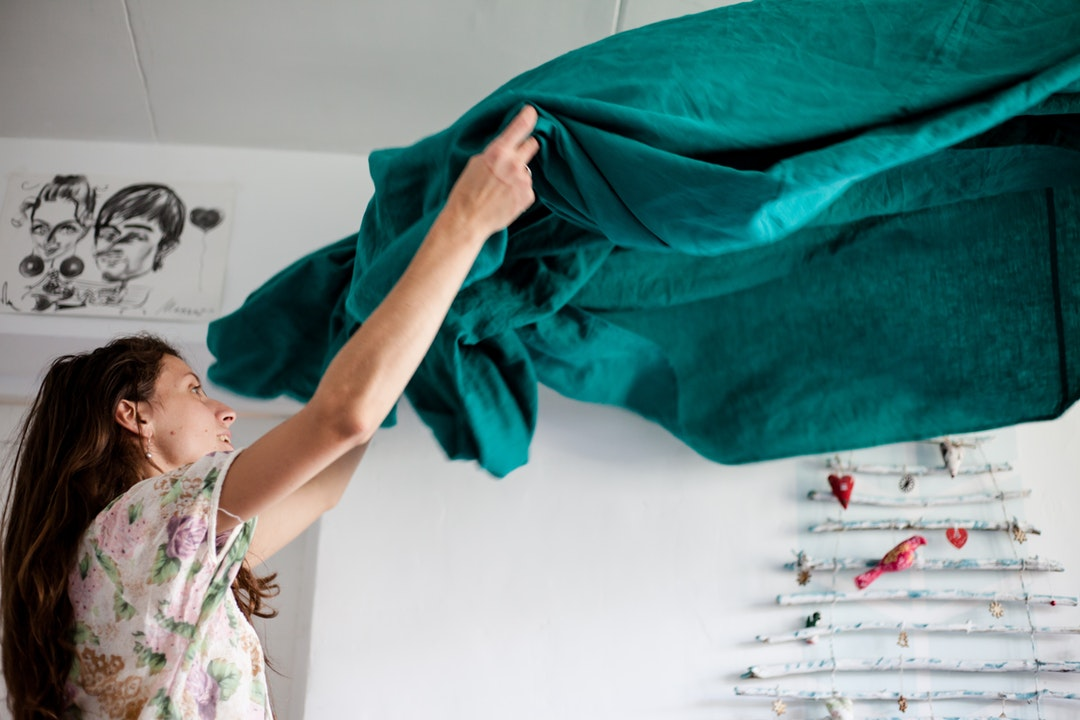 image of woman folding out sheets during an estate clean out