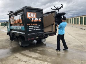 Matthew Herman of Bye Junk loading up a truck with unwanted junk
